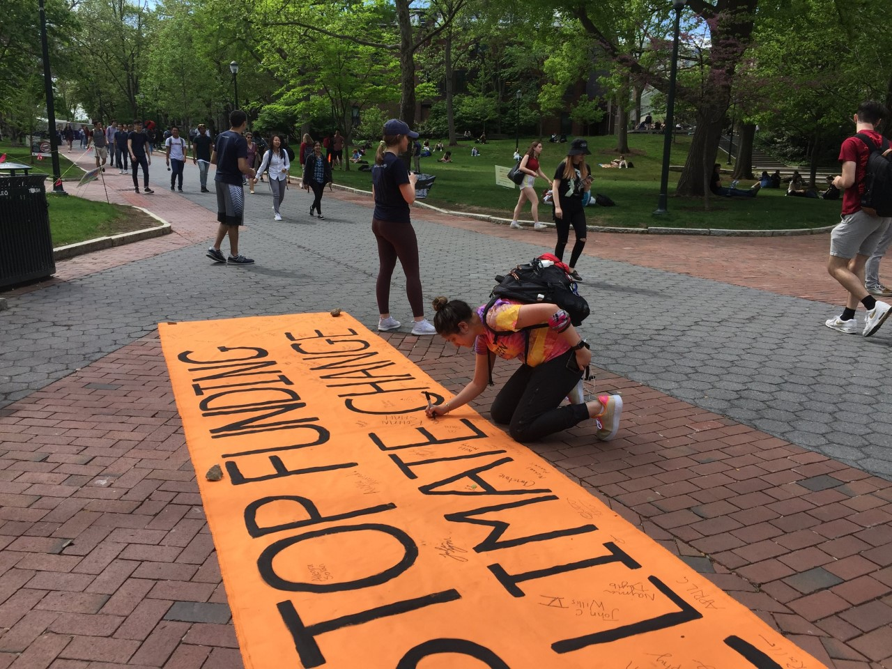 "student adds signature to banner reading ""Stop Funding Climate Change"""
