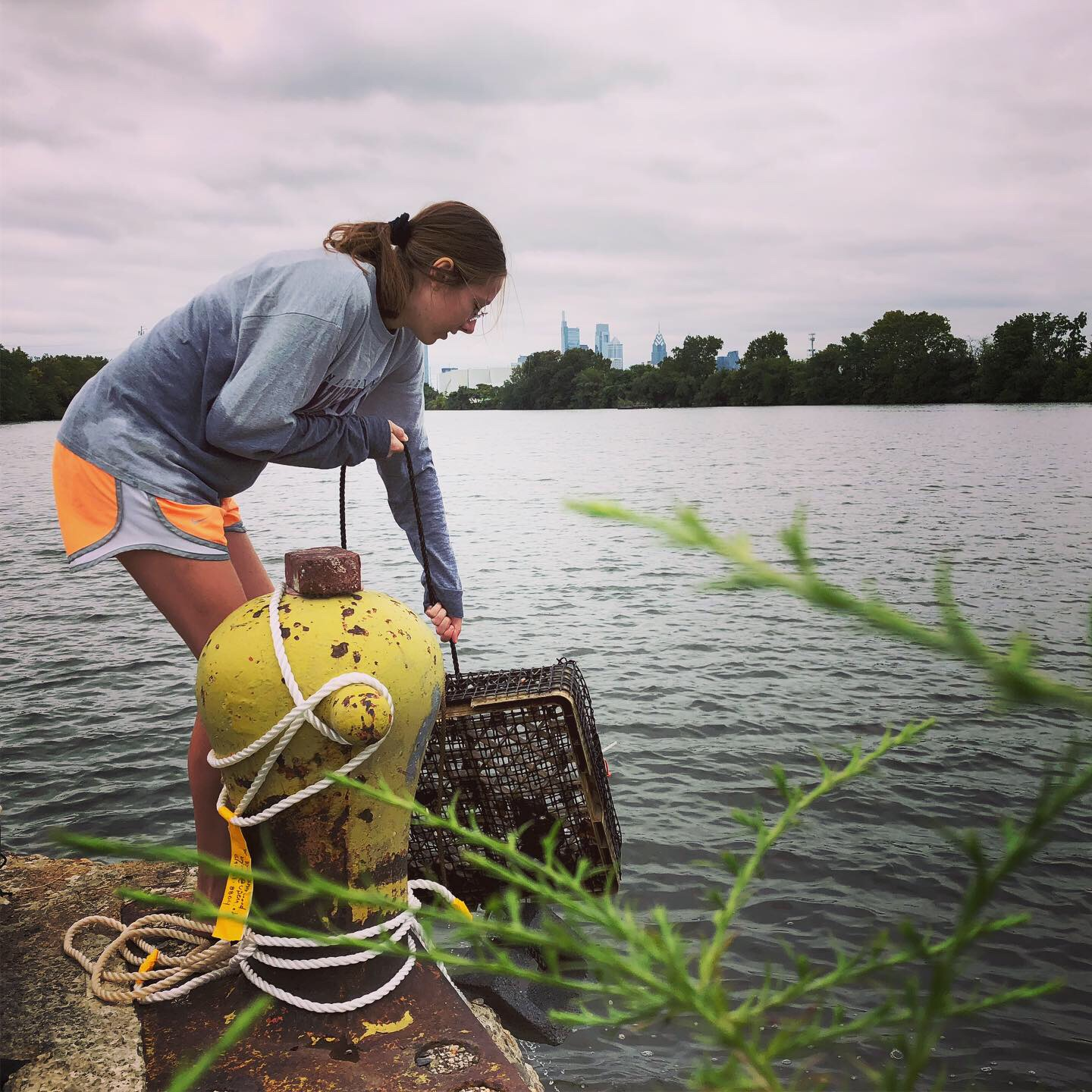 Penn Biology student, Izzy Viney, retrieves mussels from the Schuylkill River at our Bartram's Garden research and community outreach site on S. 56th street.