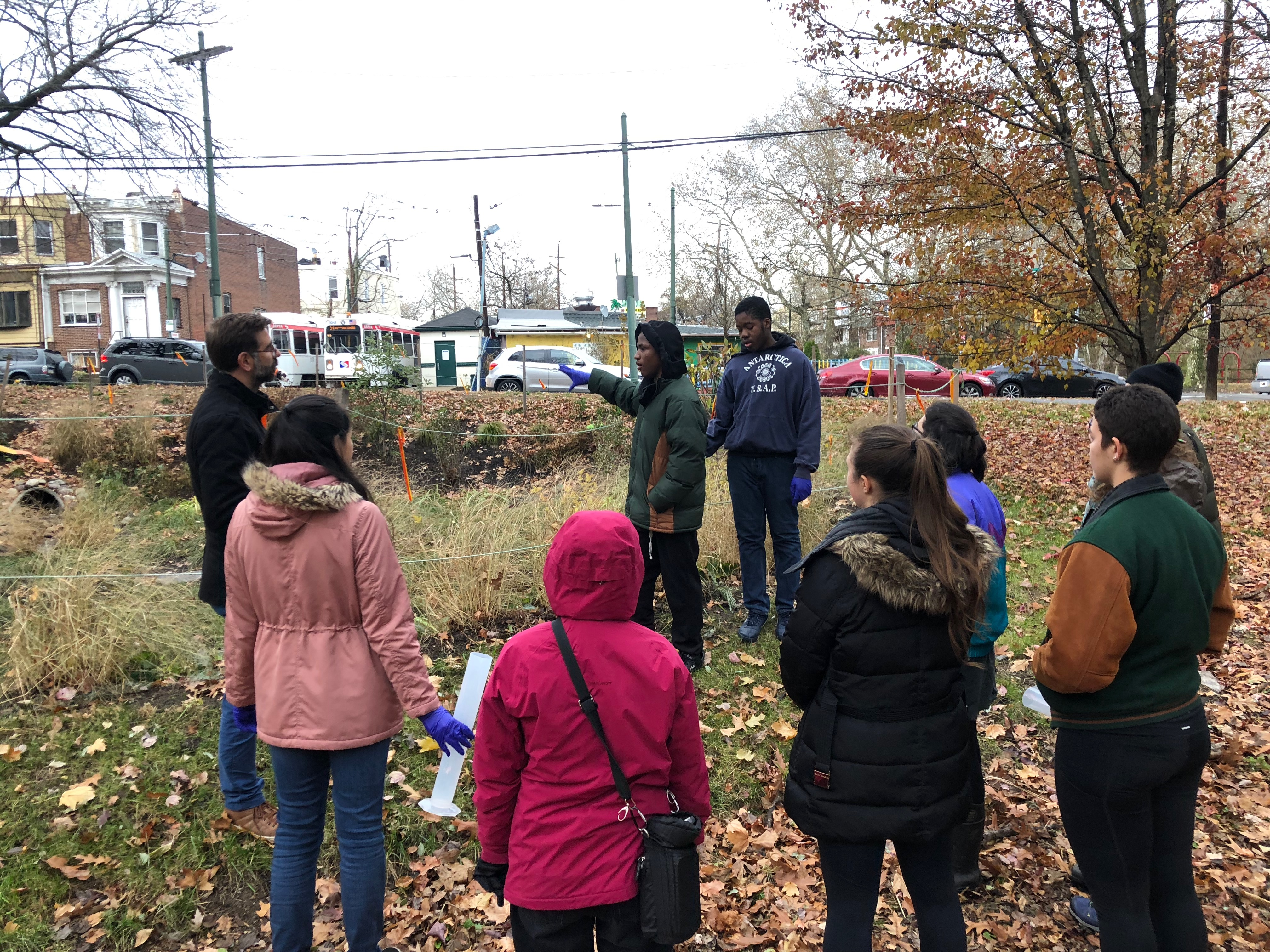 Two PWD Watershed Stewards explain the importance and function of a new rain garden on 63rd street to Penn undergraduate students.