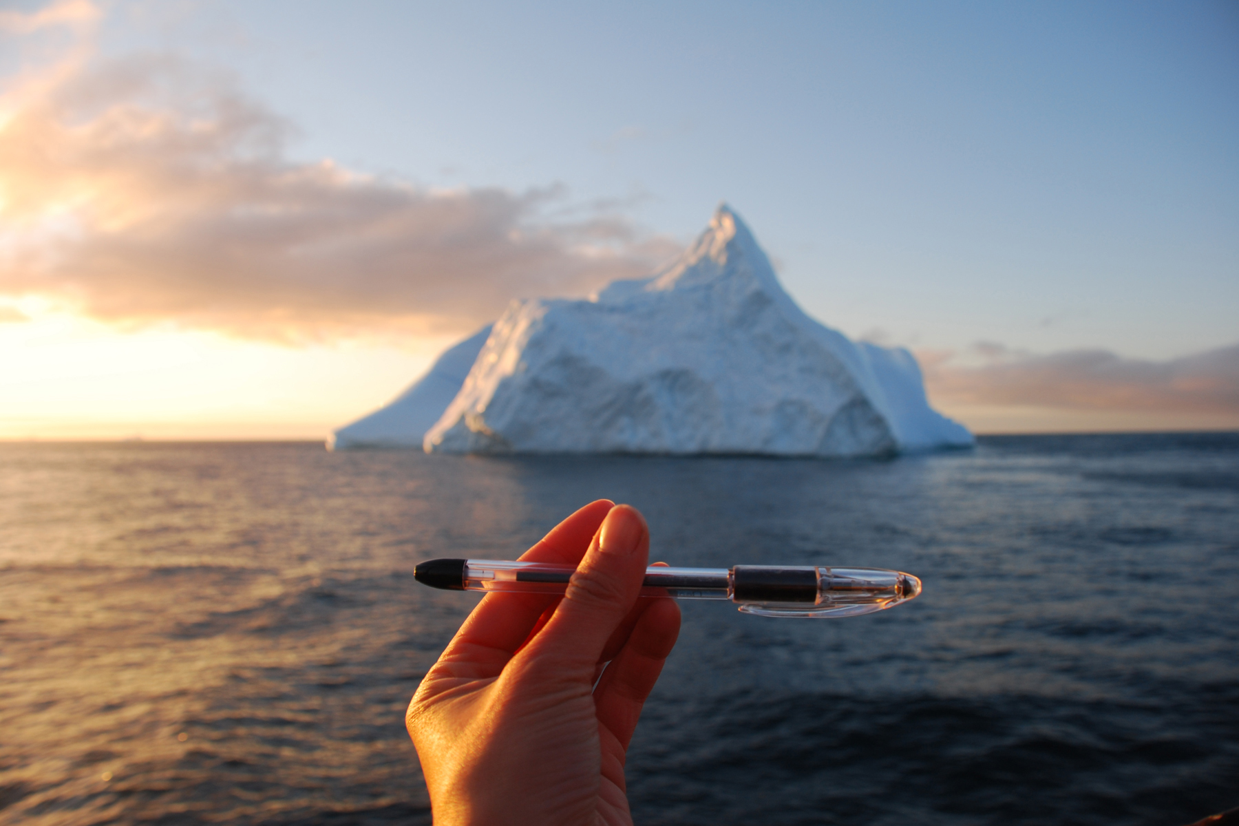iceberg with a hand and pencil in the foreground