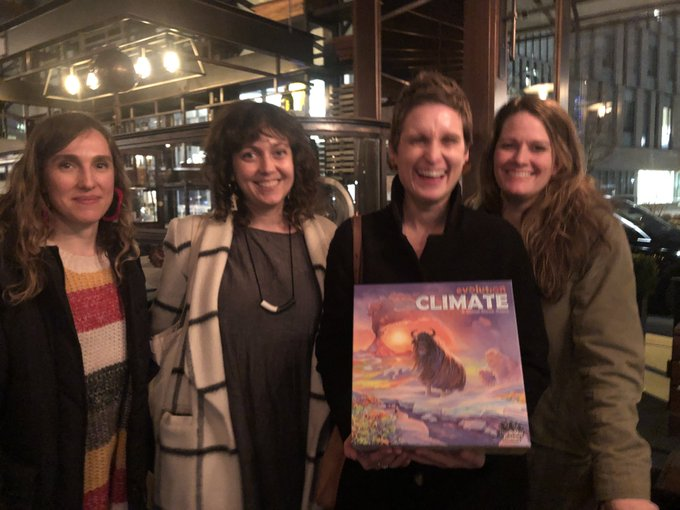 Members of Underwater New York stand next to each other in a dimly lit room, Nicole Miller holds a climate game in her arms