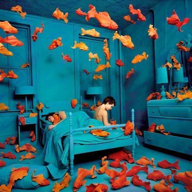 a blue hued bedroom with a child on the bed filled with orange goldfish in the air and on the floor