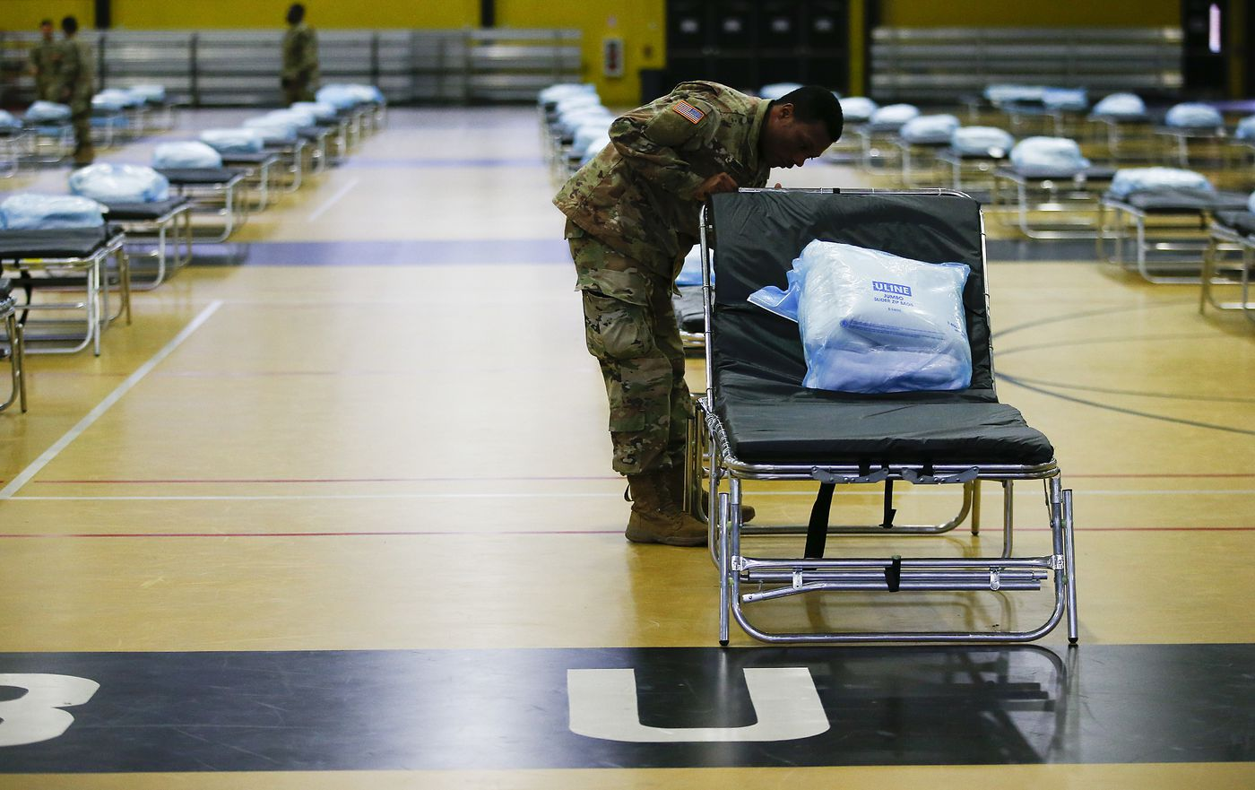 a member of the national guard sets up a hopital bed in a gymnasium