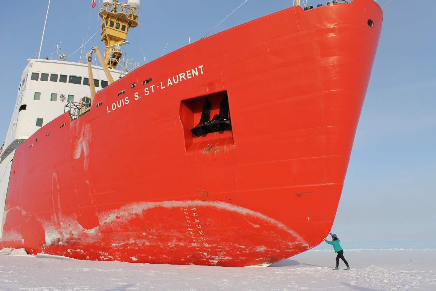 Large red  ice breaker ship fills the frame with small figure in the bottom right seeming to push the ship