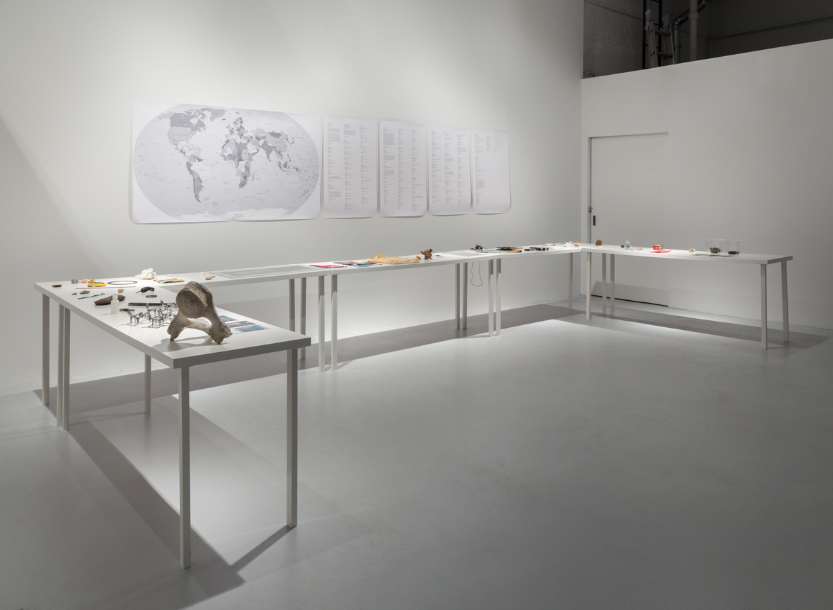 a studio setting with a 'u' shaped table with artifacts and a world map on the wall