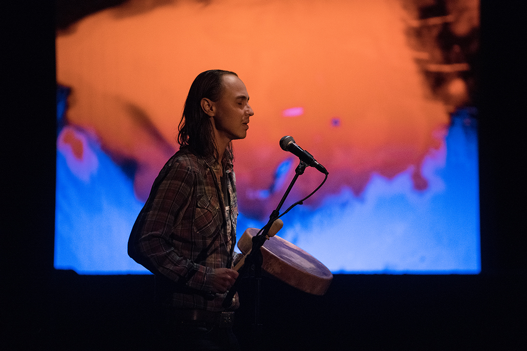 Side profile portrait of JTB in front of an orange and blue background, holding a drum and a microphone