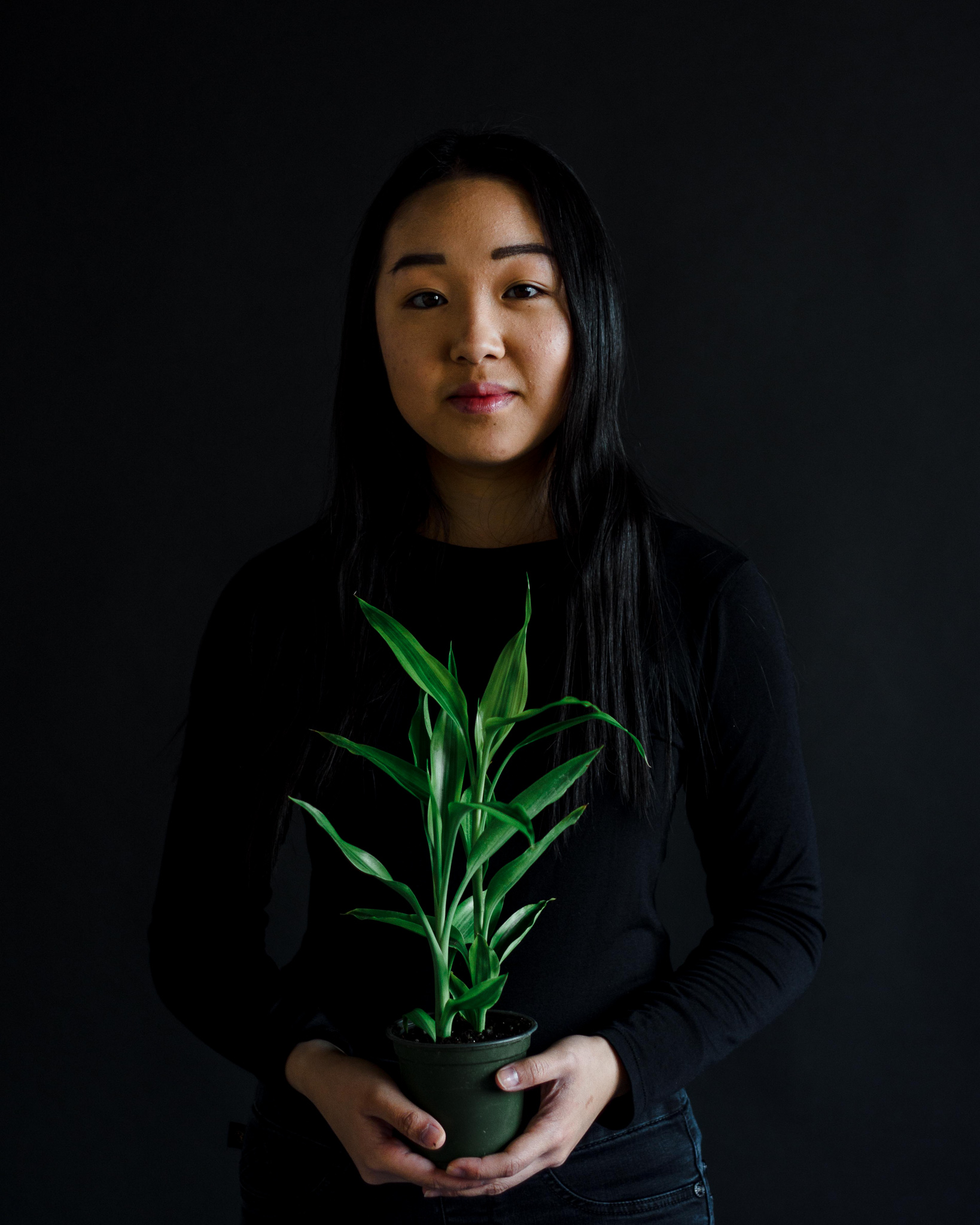 Portrait of Jess Lin holding a plant, in front of a dark field