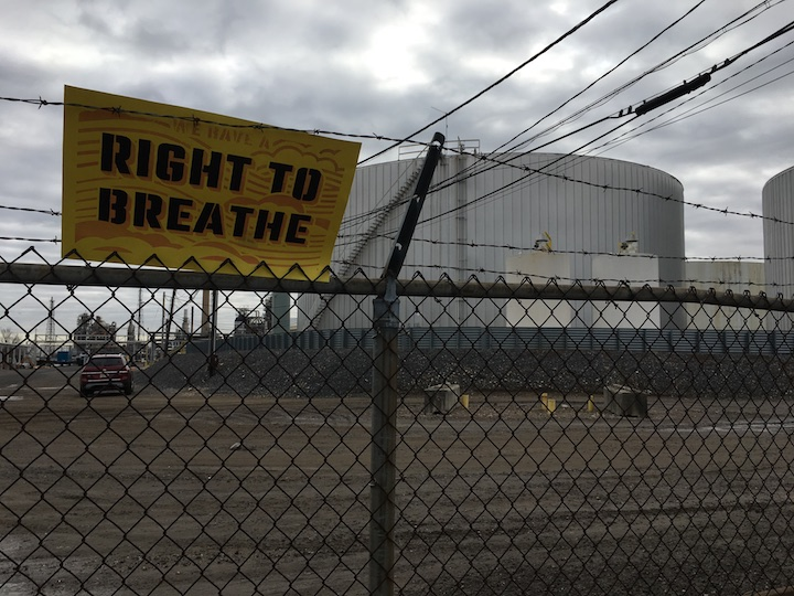 right to breathe sign on fenceline of refinery