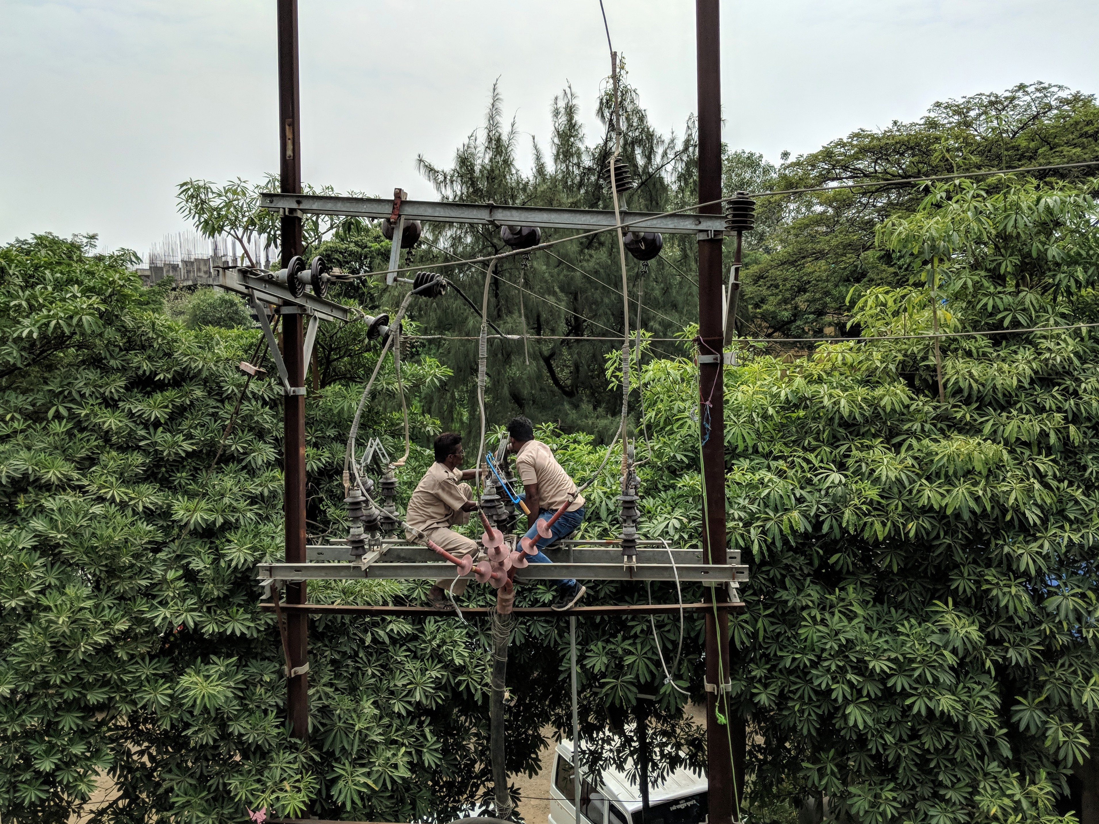 Photo of men suspended while repairing a power line in India.
