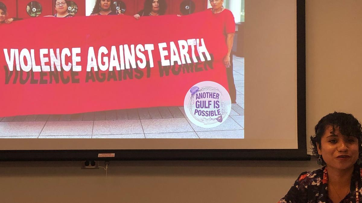 "Yudith Nieto in front of a screen with an image of Another Gulf is Possible activists holding a red banner that reads ""Violence Against Earth, Violence Against Women"""