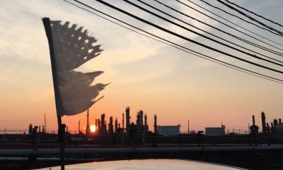tattered US flag flying over the refinery at sunset
