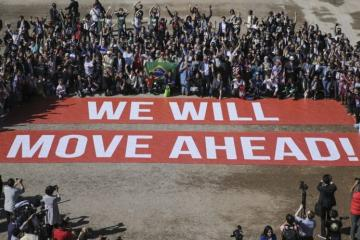Participants at COP22, a follow-up on the Paris climate agreement, stage a public show of support for climate negotiations in Marrakech, Morocco, on Nov. 18. (AP Photo/David Keyton)