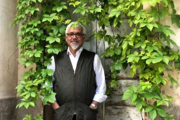 amitav ghosh against a wall with ivy