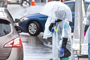 woman under an umbrella with a mask and other protective gear standing in the rain