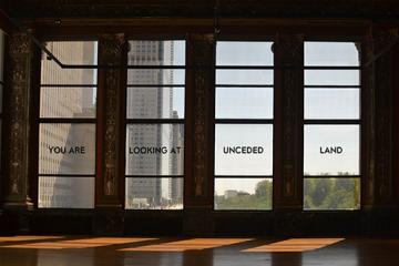 photo of windows with text reading you are on un-ceded land