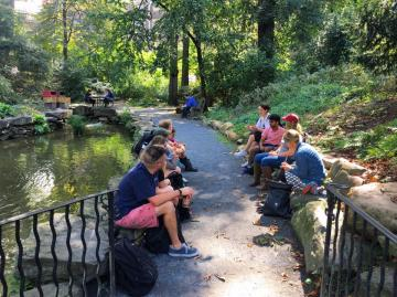 students and faculty member sitting by the biopond on the  University of Pennsylvania campus