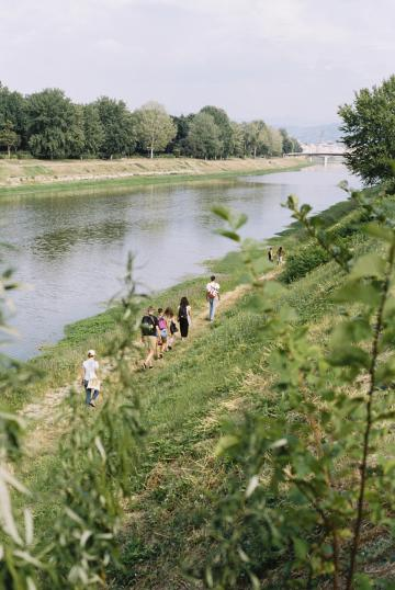 distant view of participants walking along the Arno river with vegetation in the foreground