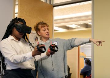 April Anson instructs a participant on using the VR headset and controls