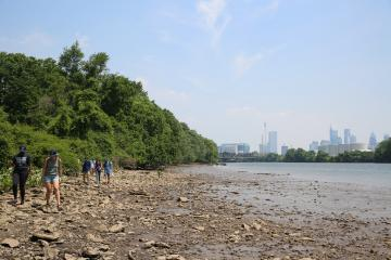 view of the schuylkill river with students on the rocky river bank in the bottom left corner